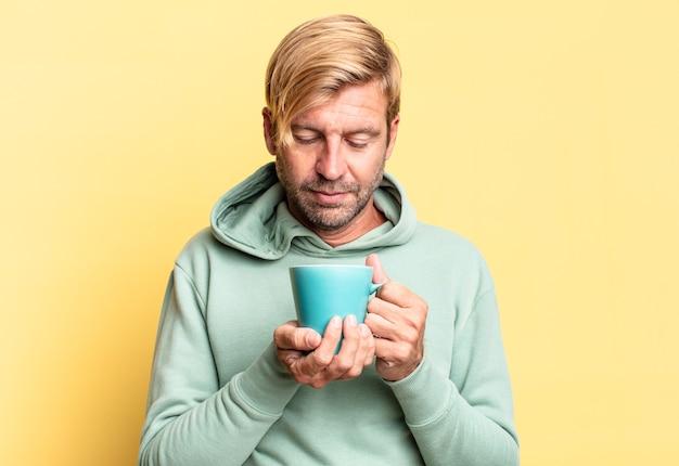 Blonde knappe volwassen man met een koffiekopje