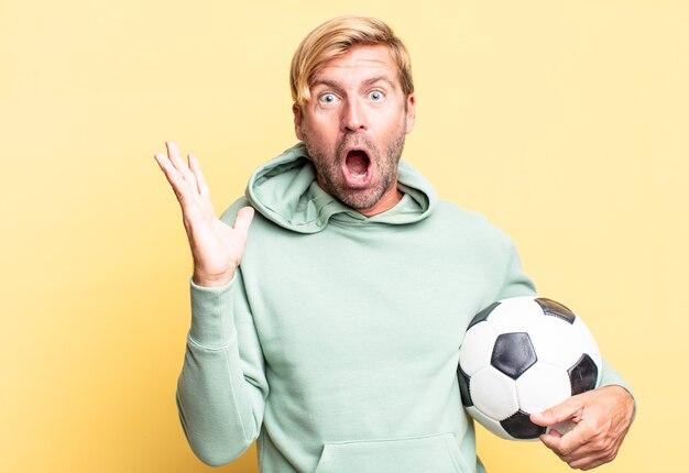 Blonde knappe volwassen man met een voetbal
