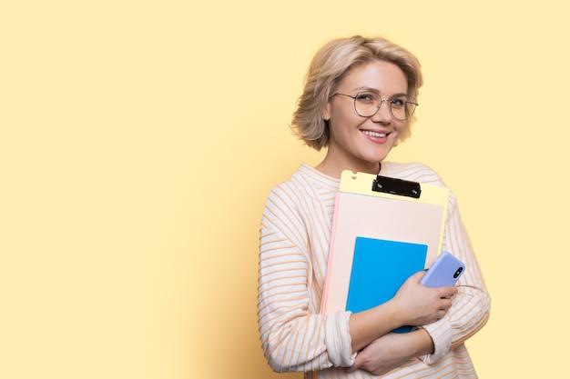 Blonde kortharige student lacht naar de camera met mappen en een telefoon die op een gele muur poseert