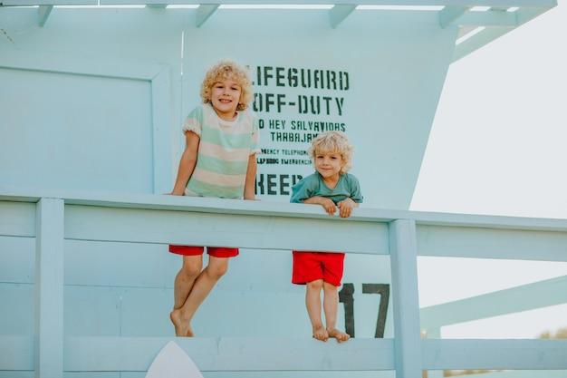 Blonde krullende jonge jongens in zomerkleren poseren bij blauwe badmeestertoren op het strand