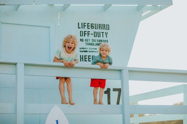 Blonde krullende jonge jongens in zomerkleren poseren bij blauwe badmeestertoren