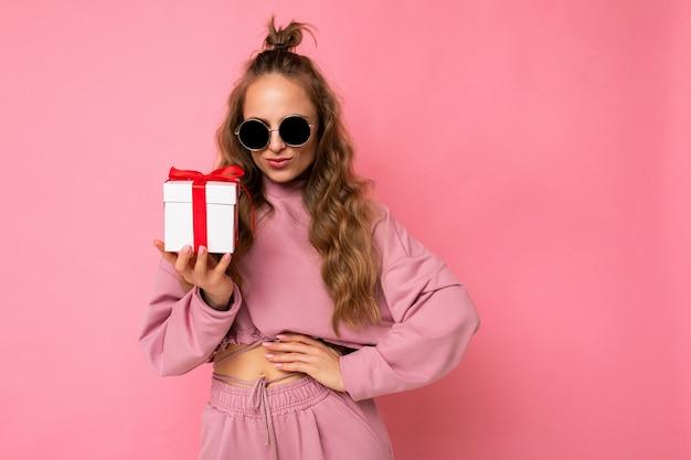 Blonde krullende vrouw die over roze muur als achtergrond wordt geïsoleerd die roze sport draagt