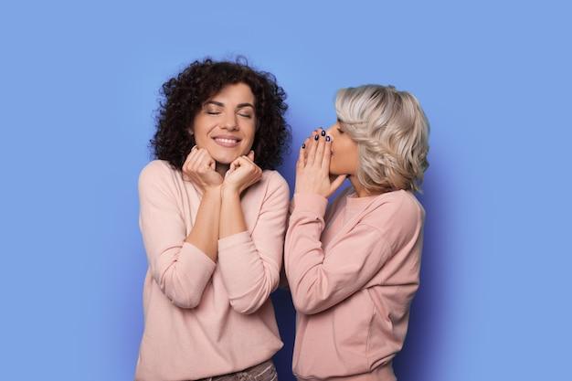 Blonde krullende vrouw fluistert iets tegen haar brunette zus glimlachend op een blauwe muur