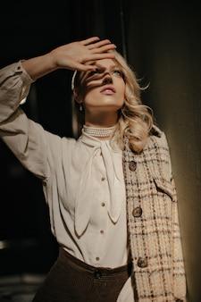 Blonde krullende vrouw in tweed jasje en witte elegante blouse bedekt zon met hand. charmant meisje kijkt op en poseert in een donkere kamer