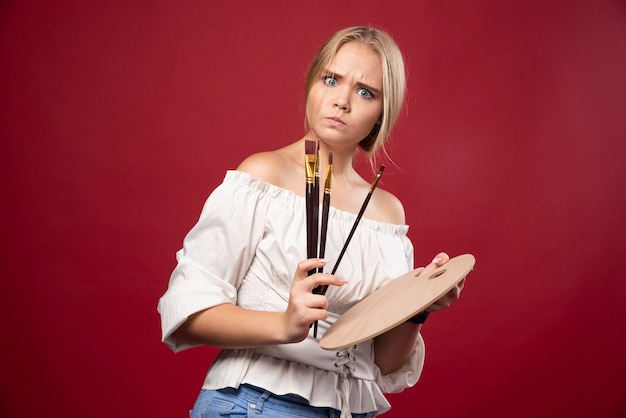 Blonde kunstenaar houdt een palet en borstels vast en kijkt verrast en verward.