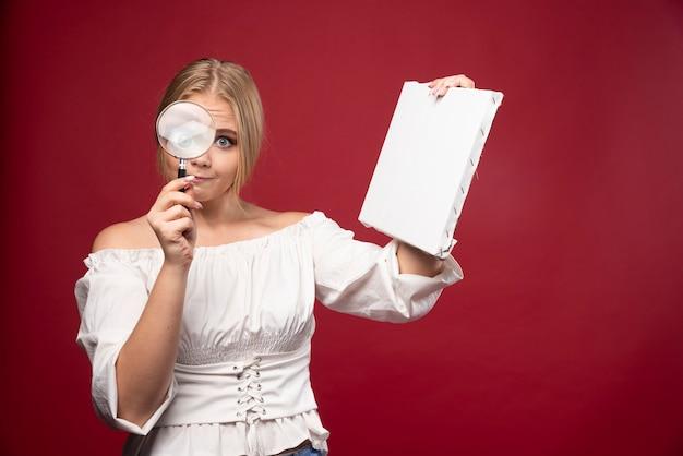 Blonde kunstmeester die het canvas controleert met een vergrootglas.