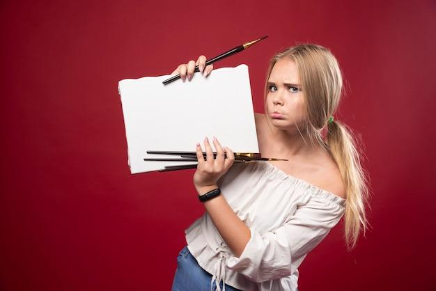 Blonde kunstmeester die op canvas met een kwast werkt en aarzelend haar kunstwerken laat zien.