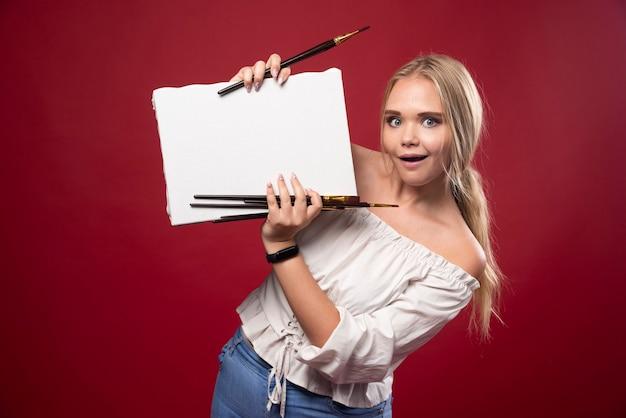 Blonde kunstmeester die op canvas met een kwast werkt en haar kunstwerken met vertrouwen laat zien.