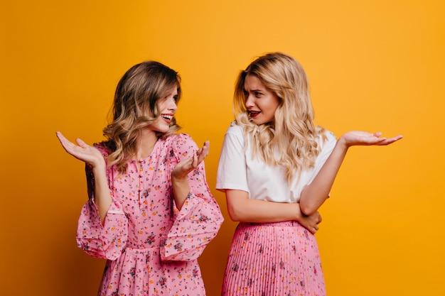 Blonde leuke vrouw die haar zus bekijkt. binnenfoto van charmante witte dames die op gele muur spreken.