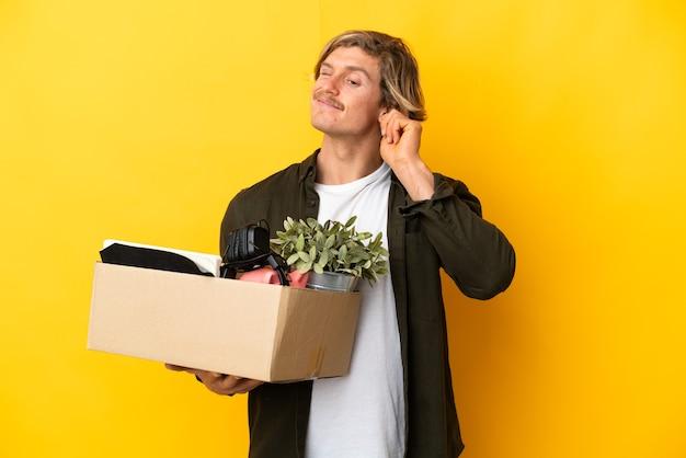 Blonde man die een zet doet terwijl hij een doos vol dingen oppakt die geïsoleerd zijn op een gele achtergrond, gefrustreerd en oren bedekt