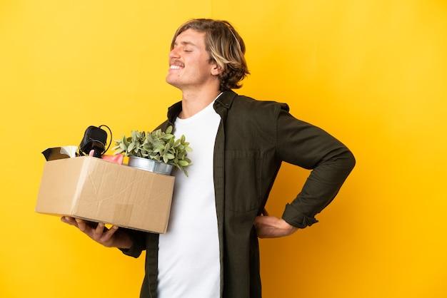 Blonde man die een zet doet terwijl hij een doos vol dingen oppakt die op een gele achtergrond worden geïsoleerd, die lijden aan rugpijn omdat ze zich hebben ingespannen