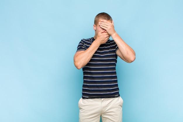 Blonde man die gezicht bedekt met beide handen en nee zegt tegen de camera! afbeeldingen weigeren of foto's verbieden
