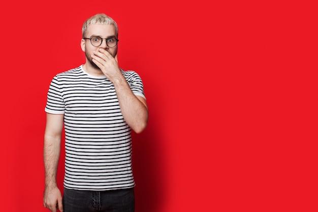 Blonde man gebaren verrassing bril op het bedekken van mond met palm op een rode muur