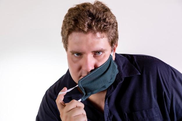 Blonde man in glazen met zelfgemaakte masker voor bescherming tegen coronavirus geïsoleerd op een witte muur