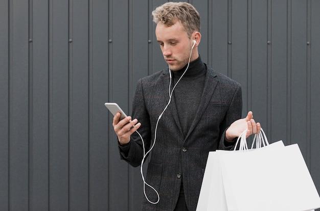 Blonde man in het zwart kijken naar smartphone