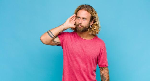 Blonde man kijkt serieus en nieuwsgierig, luistert, probeert een geheim gesprek of roddel te horen, afluistert