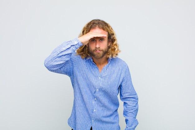 Blonde man kijkt verbijsterd en verbaasd, met hand over het voorhoofd kijkt ver weg, kijkt of zoekt