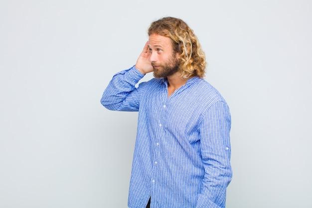 Blonde man lacht, kijkt nieuwsgierig naar de zijkant, probeert te roddelen of een geheim af te luisteren