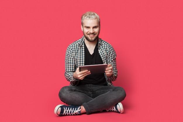 Blonde man met baard zit op de grond met een tablet op een rode muur