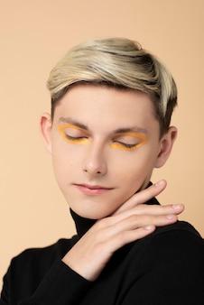 Blonde man met oranje eyeliner