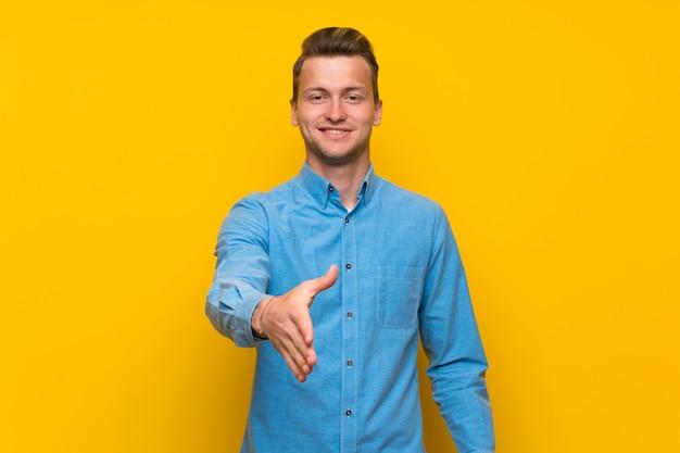 Blonde man over geïsoleerde gele muur handen schudden voor het sluiten van een goede deal