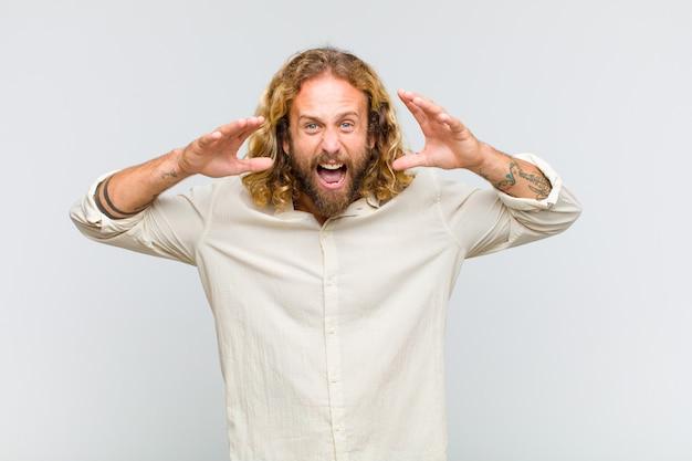 Blonde man schreeuwt van paniek of woede, geschokt, doodsbang of woedend, met de handen naast het hoofd