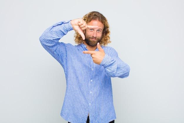 Blonde man voelt zich gelukkig, vriendelijk en positief, lacht en maakt een portret of fotolijst met handen