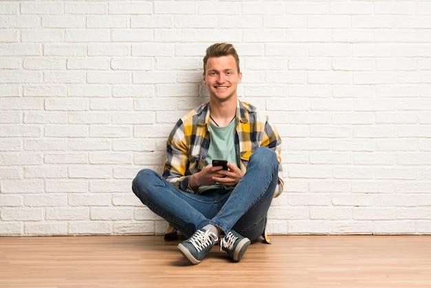 Blonde man zittend op de vloer een bericht sturen met de mobiel