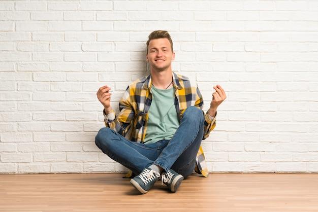 Blonde man zittend op de vloer geld gebaar maken