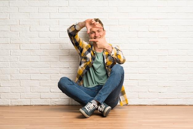 Blonde man zittend op de vloer gericht gezicht, framing symbool