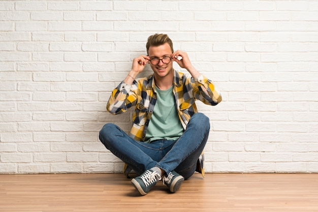 Blonde man zittend op de vloer met een bril en verrast