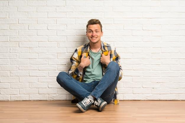 Blonde man zittend op de vloer met verrassing gezichtsuitdrukking
