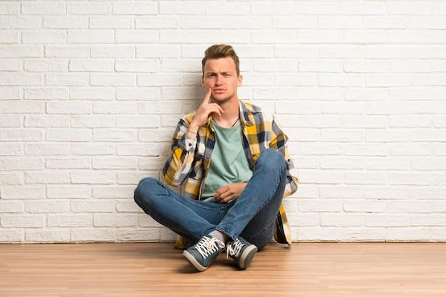 Blonde man zittend op de vloer op zoek naar voren