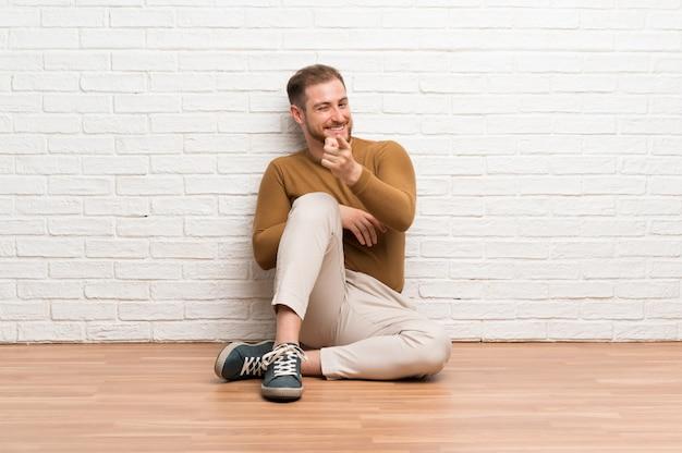 Blonde man zittend op de vloer wijst vinger naar je