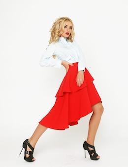 Blonde mannequin met luxe haar en rode rok in studio op witte achtergrond