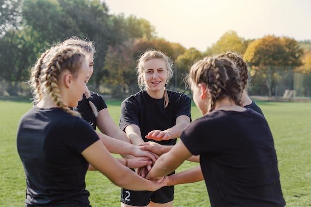 Blonde meisjes die handen samenbrengen