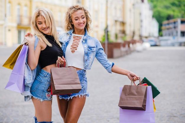Blonde meisjes staan buiten zakken zakken lachend