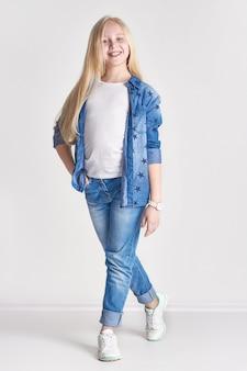 Blonde meisjestiener in een denimkostuum, pretkind fashionrt het stellen