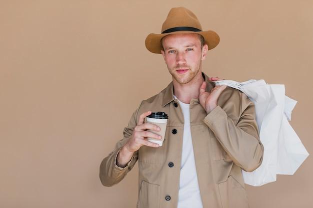 Blonde mens die met koffie aan de camera kijkt