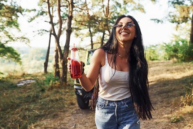 Blonde met alcohol in de hand maakt een wandeling in het bos tegen groene jeep.