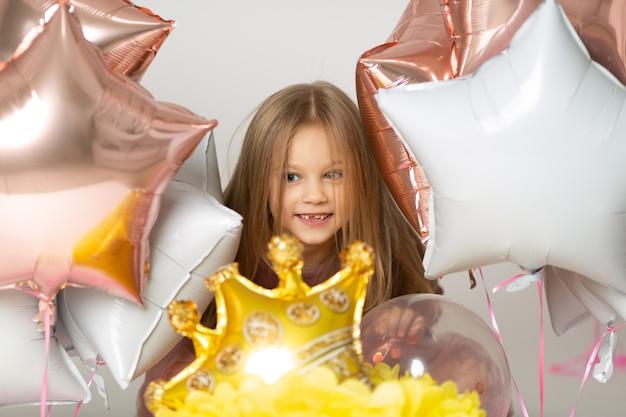 Blonde met blauwe ogen lacht en speelt met ballonnen