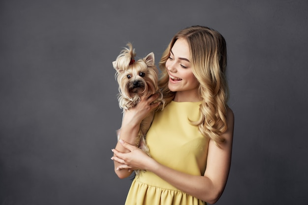Blonde met een kleine hond make-up poseren geïsoleerde achtergrond