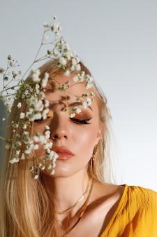 Blonde met heldere herfstmode make-up en schaduw van bloemen op haar gezicht. detailopname.