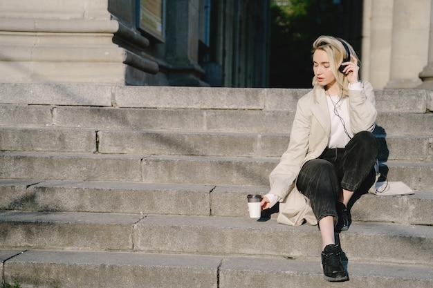 Blonde met koptelefoon zittend op een trap