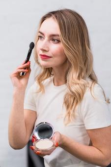 Blonde met poeder die make-up met borstel toepassen