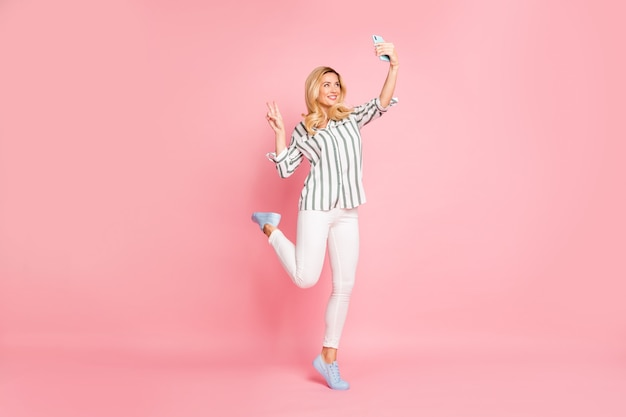 Blonde modieuze dame poseren tegen de roze muur