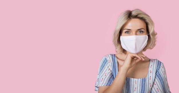 Blonde modieuze vrouw draagt een medisch masker op het gezicht en het aanraken van haar kin maakt reclame voor iets op een roze muur met vrije ruimte