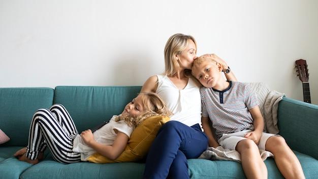 Blonde moeder die het hoofd van haar zoon kust en met dochter op de bank ontspant