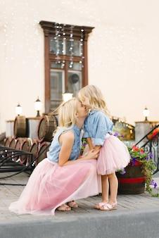 Blonde moeder en dochtertje in roze rokken en denim shirts kijken elkaar aan