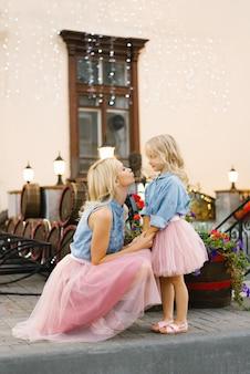Blonde moeder en dochtertje in roze rokken en denim shirts kijken elkaar aan.